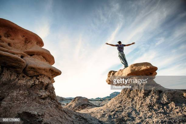 a man doing parkour on rocks in the desert - robb reece stockfoto's en -beelden