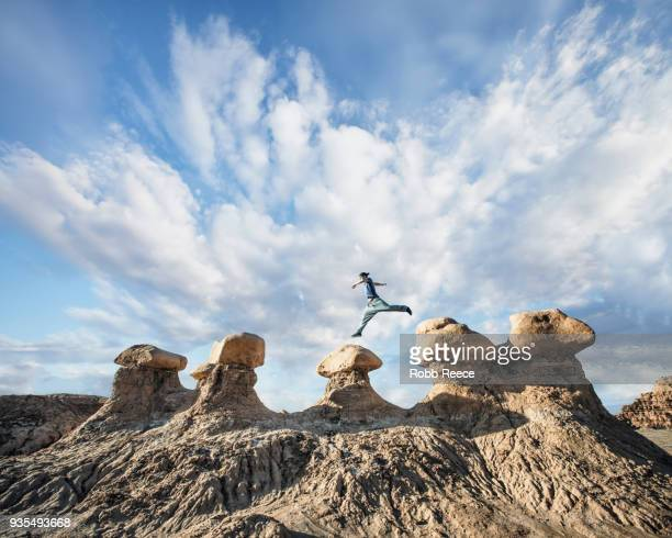 a man doing parkour on rocks in the desert - robb reece stock pictures, royalty-free photos & images
