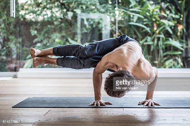 Man doing Parsva Bakasana in studio