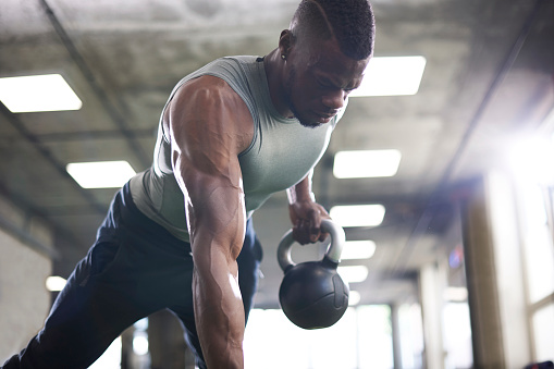 Man doing plank with kettlebells in gym - gettyimageskorea