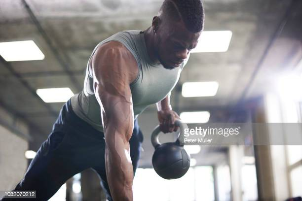 man doing plank with kettlebells in gym - sports training stock pictures, royalty-free photos & images