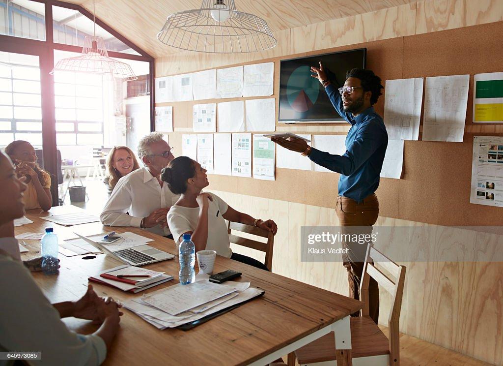 Man doing presentation, using tablet & screen : Stock Photo