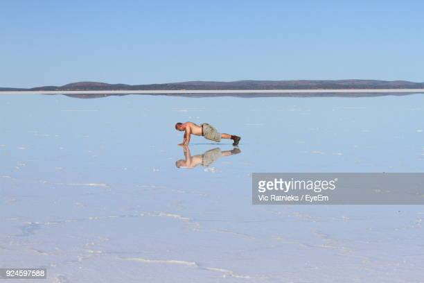 man doing press-ups at beach against sky - ratnieks stock pictures, royalty-free photos & images