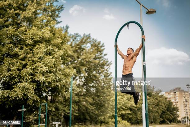 男のプルを行う地元の公園で ups - 自重トレーニング ストックフォトと画像