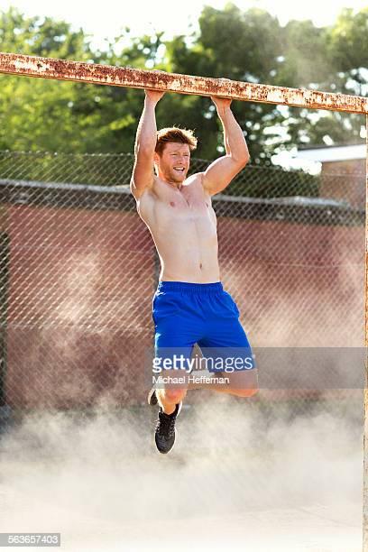Man doing pull ups on goal post