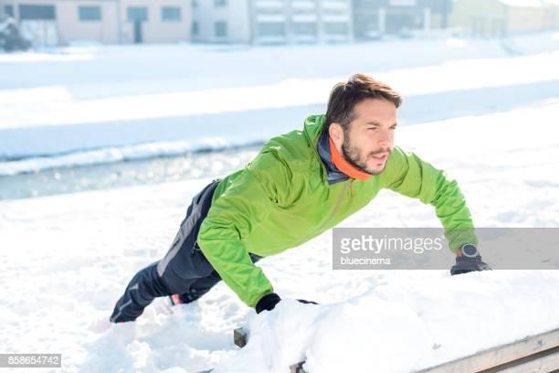 Mann tun Liegestütze im Freien in einem park auf der Bank
