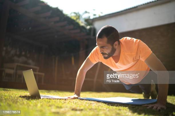 man doing push-ups during a virtual exercise class - self improvement stock pictures, royalty-free photos & images