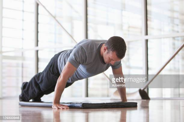 man doing push-ups in health club - plank exercise stock pictures, royalty-free photos & images