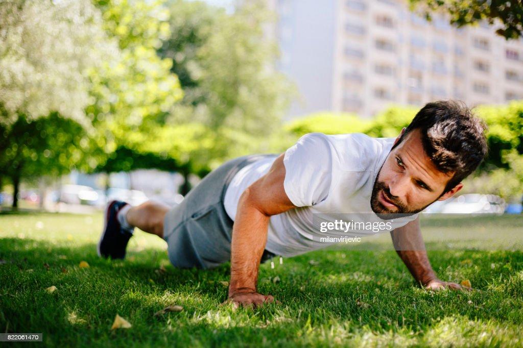 Man doing pushups in nature : Stock Photo