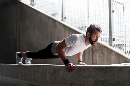 Man doing push-ups on concrete wall - gettyimageskorea