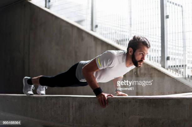 man doing push-ups on concrete wall - sport stock-fotos und bilder