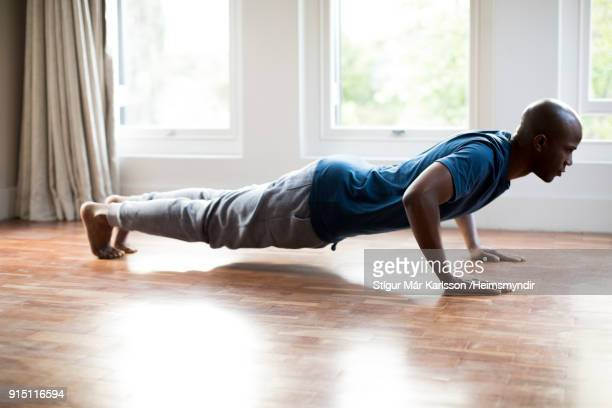 man doing push-ups on hardwood floor at home - push ups stock pictures, royalty-free photos & images