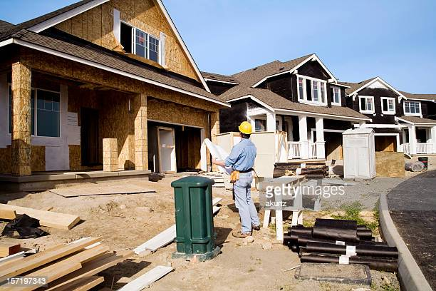 Man doing quality control inspection of a house being built