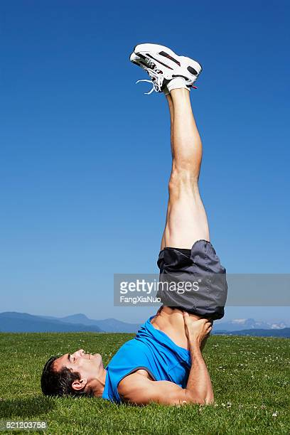 man doing shoulder stand - ease stock pictures, royalty-free photos & images