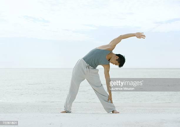 Man doing side stretch on beach