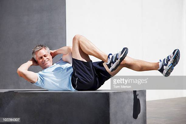 man doing sit-ups in urban setting - sit ups stock photos and pictures