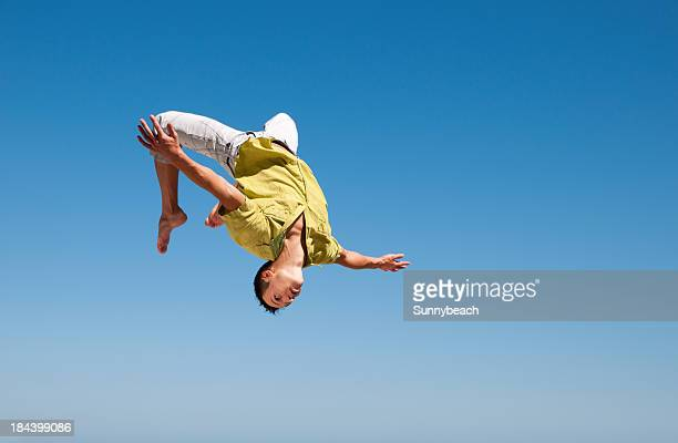 Man doing somersault in the air against blue sky