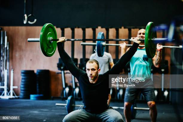 Man doing squats with barbell overhead
