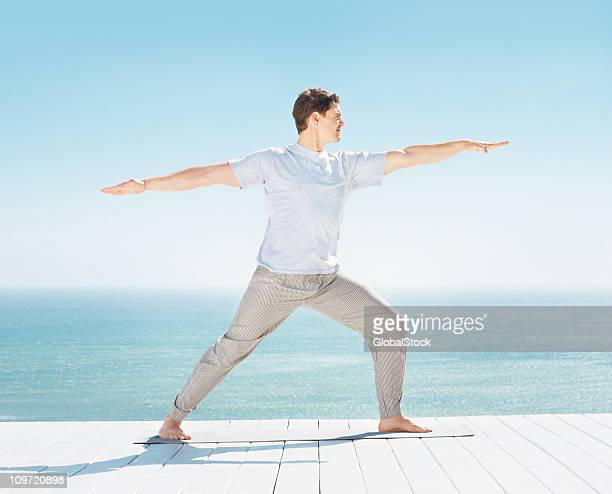 Man doing stretching exercise on wooden pier by the sea