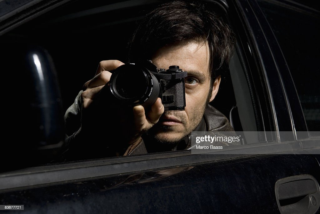 A man doing surveillance with a camera from his car : Stock Photo