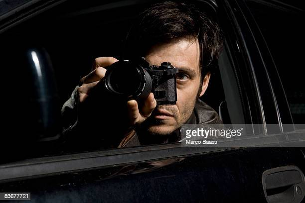 a man doing surveillance with a camera from his car - spionage und aufklärung stock-fotos und bilder