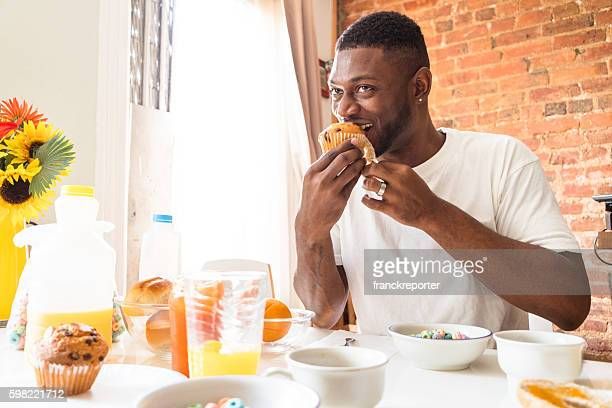 man doing the breakfast at home with muffin