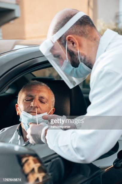 車の窓からタンポンをしている男 - ドライブスルー検査 ストックフォトと画像