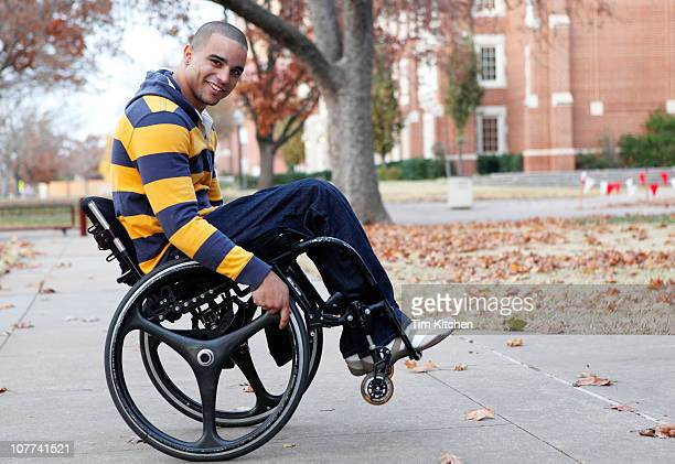 Man doing trick in wheelchair on campus, smiling