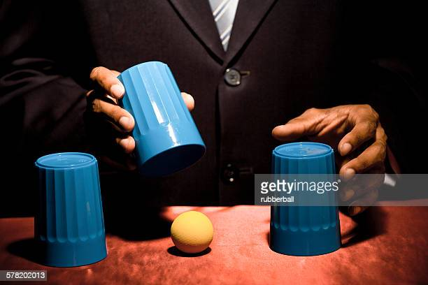Man doing trick with three cups