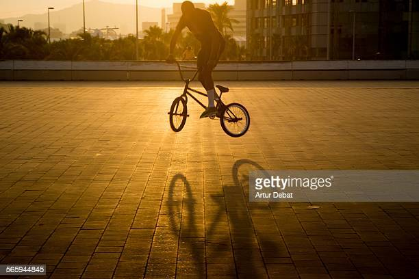 Man doing tricks with BMX and shadow on sunset.
