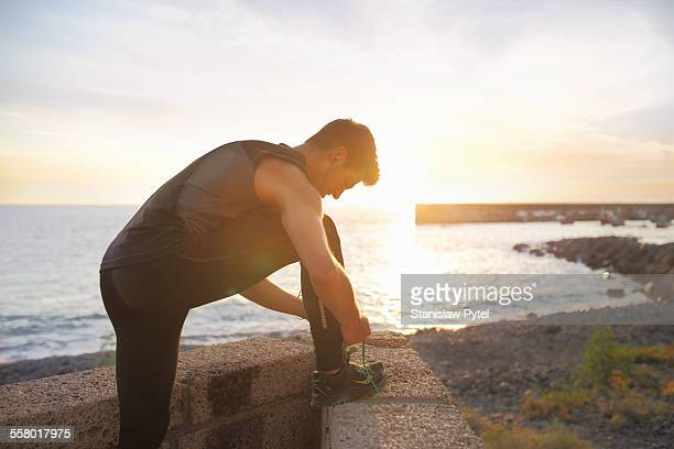 Man doing up shoes, workout near ocean at sunset