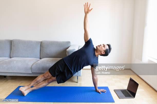 man doing yoga at home during coronavirus lockdown - 体への関心 ストックフォトと画像