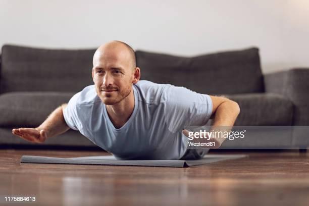 man doing yoga at home - liggen stockfoto's en -beelden
