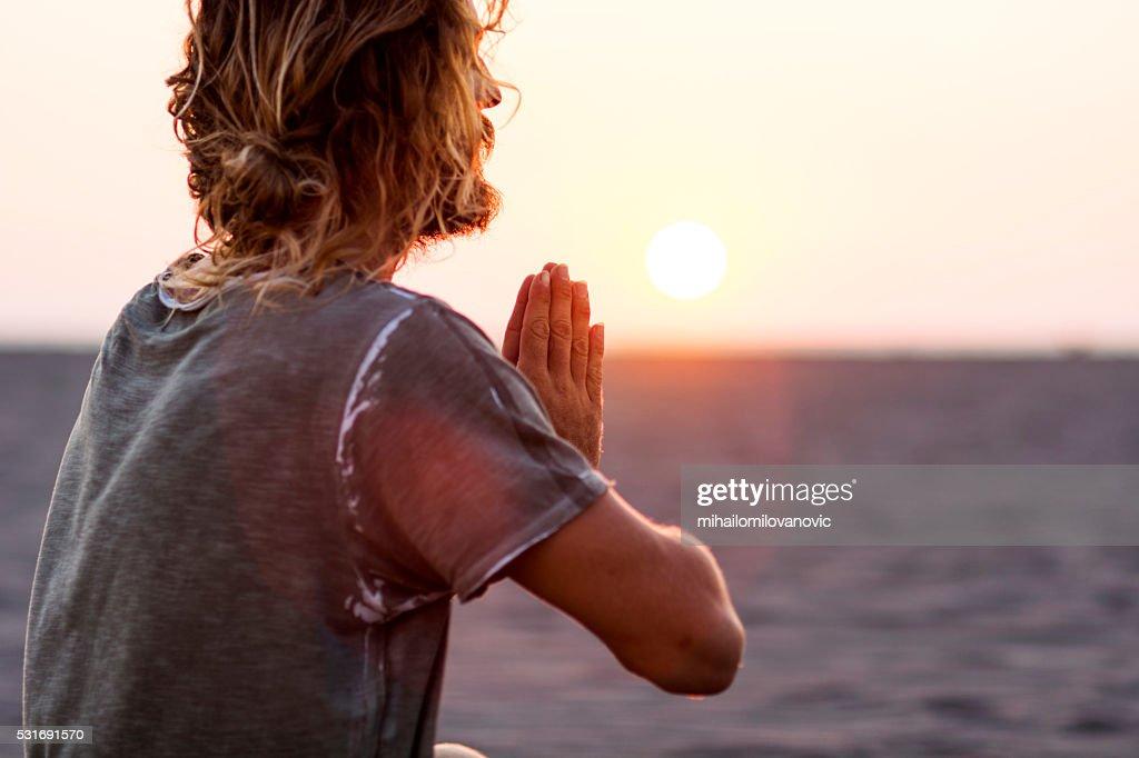 Man doing yoga at the beach : Stock Photo
