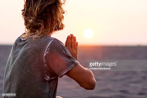Uomo fare yoga alla spiaggia