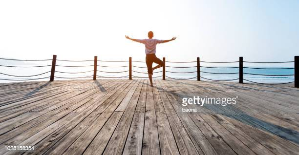man doing yoga at the seaside - standing on one leg stock pictures, royalty-free photos & images