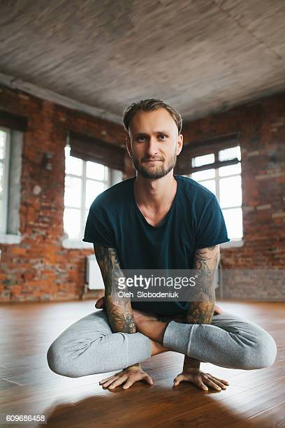 man doing yoga in studio - yoga teacher stock pictures, royalty-free photos & images