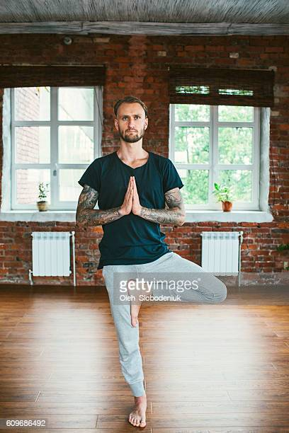 man doing yoga in studio - tree position stock photos and pictures