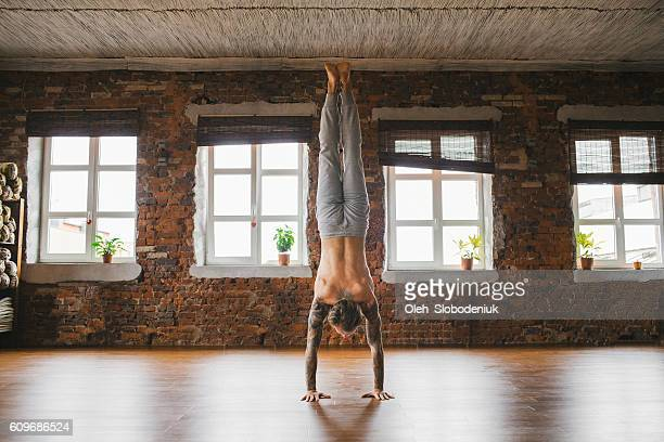 man doing yoga in studio - handstand stock pictures, royalty-free photos & images
