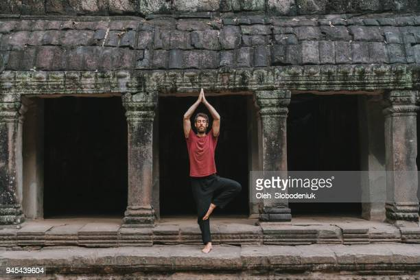 man doing yoga in temple angkor wat - monk stock pictures, royalty-free photos & images