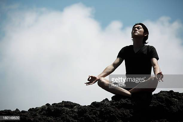 man doing yoga in the mountain