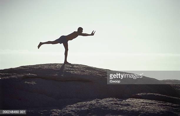 Man doing yoga on hill