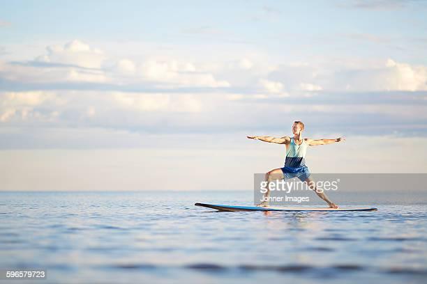 Man doing yoga on paddleboard