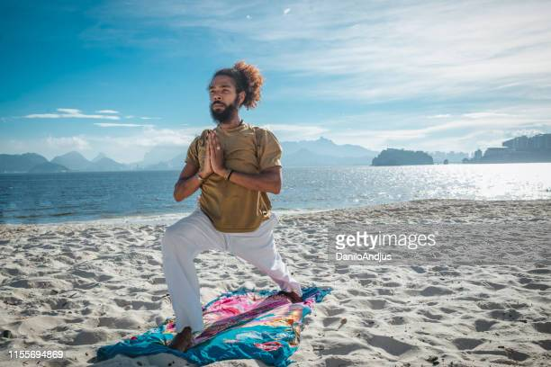 man doing yoga on the beach - acrobatic activity stock pictures, royalty-free photos & images