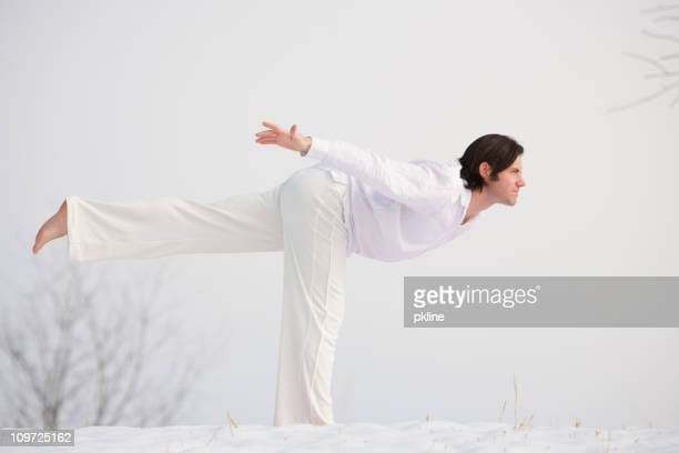 Man Doing Yoga Stretches in Snow