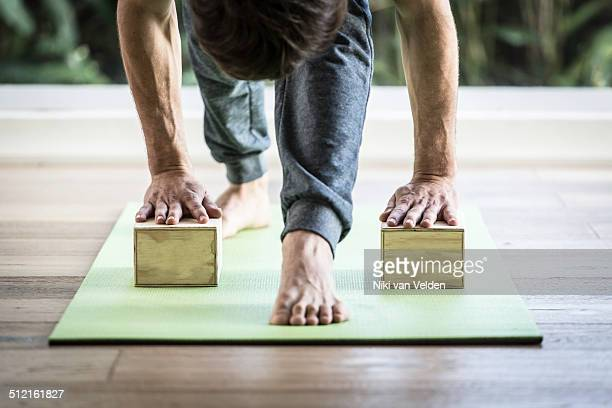 Man doing yoga with blocks in yoga studio