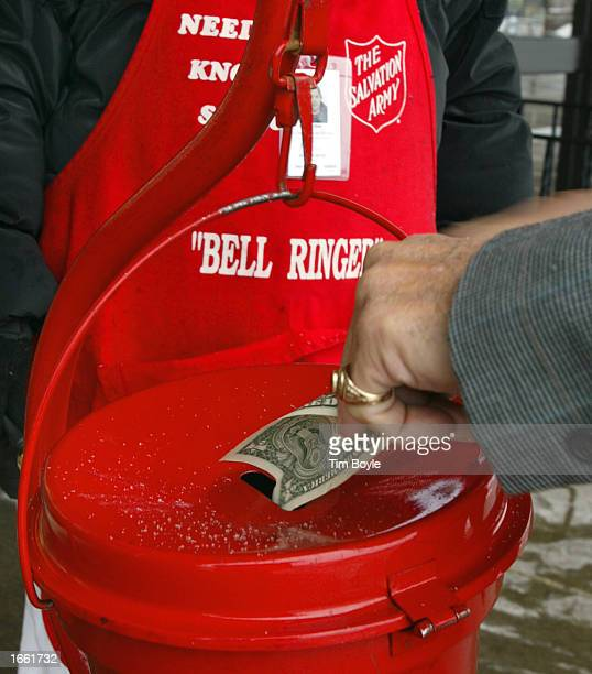 A man donates a dollar bill into the bucket of Salvation Army bell ringer Fabiola Ortiz November 26 2002 outside a JewelOsco food store in Des...
