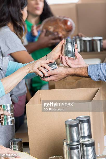 man donates canned goods at food bank - food drive stock pictures, royalty-free photos & images