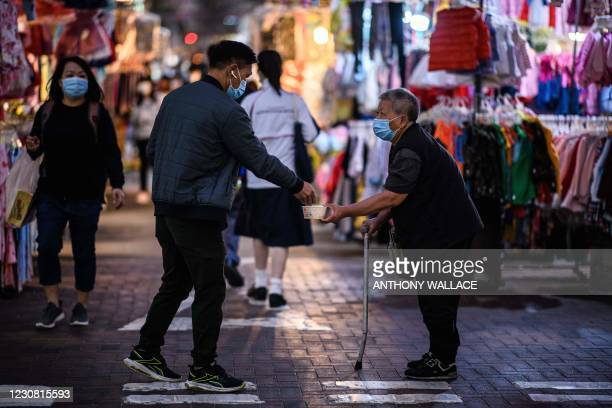 Man donates money to a person begging in the Sham Shui Po district of Kowloon in Hong Kong on January 27 one of the international business hub's...