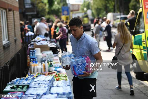 A man donates water to a stall which has been set up to help people near the burning 24 storey residential Grenfell Tower block in Latimer Road West...